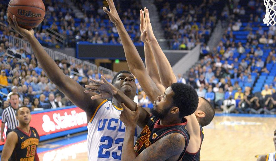 UCLA forward Tony Parker shoots as Southern California forward Malik Martin, center, and forward Nikola Jovanovic defend during the first half of an NCAA college basketball game, Wednesday, March 4, 2015, in Los Angeles. (AP Photo/Mark J. Terrill)