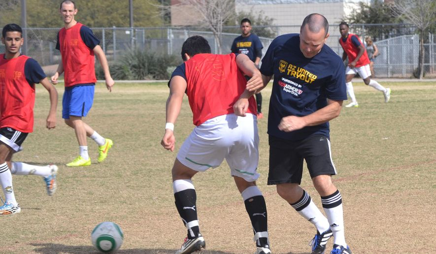 In this Feb. 14, 2015, photo, Associated Press sports writer John Marshall, right, competes during Arizona United Soccer Club tryouts in Tempe, Ariz. (AP Photo/Arizona United, Garrett Cleverly)
