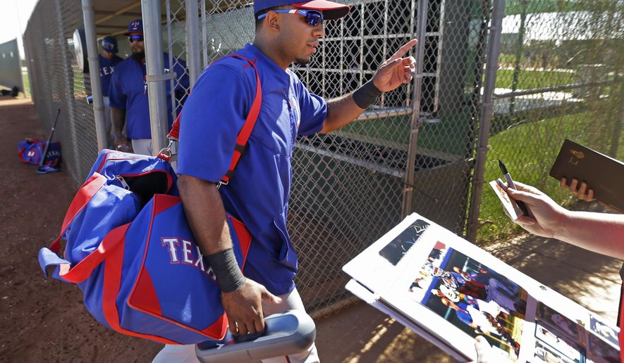 Texas Rangers' Elvis Andrus waves to autographs seekers as he walks between drills during spring training baseball practice Friday, Feb. 27, 2015, in Surprise, Ariz. (AP Photo/Charlie Riedel)