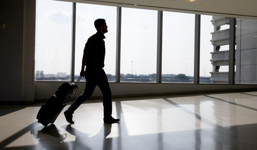 In this July 31, 2014 photo, a traveler passes through Philadelphia International Airport Thursday, in Philadelphia. (AP Photo/Matt Rourke)
