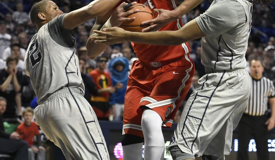 Ohio State center Amir Williams, center, drives to the basket between Penn State guard D.J. Newbill (2), and Brandon Taylor right, during an NCAA college basketball game Wednesday, March 4, 2015, in State College, Pa.  (AP Photo/John Beale)