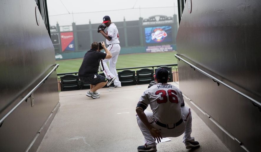 Atlanta Braves pitcher Mike Minor, right, pretends to catch for teammate Julio Teheran, rear, as he goes through the motion of a pitch for a photographer during photo day at the team's spring training baseball facility, Monday, March 2, 2015, in Kissimmee, Fla. (AP Photo/David Goldman)