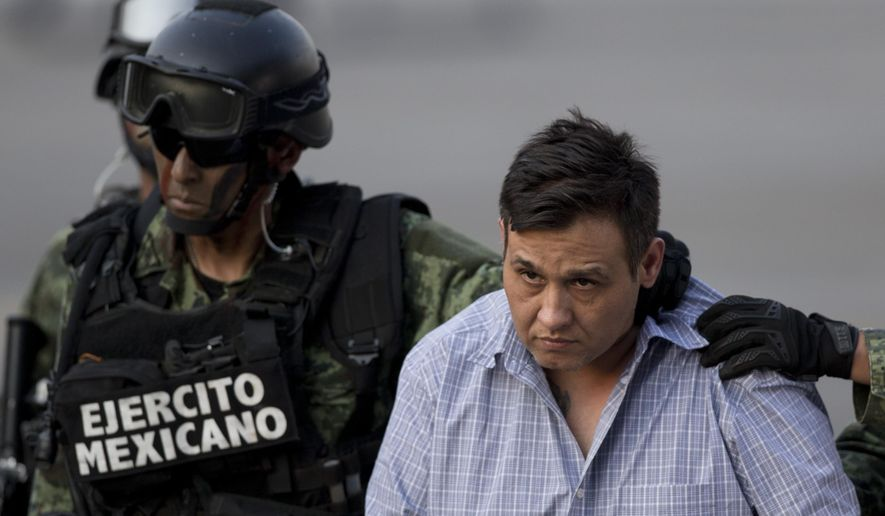 """A soldier escorts a man who authorities identified as Omar Trevino Morales, alias """"Z-42,"""" leader of the Zetas drug cartel, at the Attorney General's Office hangar in Mexico City, Wednesday, March 4, 2015. An official who was not authorized to be quoted by name because of government policy, said Morales was arrested on Wednesday in a pre-dawn raid in San Pedro Garza Garcia, a wealthy suburb of the northern city of Monterrey. (AP Photo/Eduardo Verdugo)"""