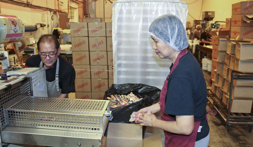 ADVANCE FOR SUNDAY MARCH 8 AND THEREAFTER  In this photo taken Feb. 27, 2015, Lyle Kobashigawa of Kauai Kookie Ko. makes adjustments on the specialty item packing machinery while Perla Soriano, right, collects the packed cookies at the Hanapepe, Hawaii facility. In the background, a crew packages the firm's salad dressing. Merchandise exports from Hawaii soared to $1.5 billion last year, a new record high that contributed to the nearly $2.35 trillion in goods and services exported nationwide. The news from the U.S. Department of Commerce came as no surprise to company officials and business advocates on Kauai, who say that exports are indeed growing. (AP Photo/The Garden Island, Darin Moriki)
