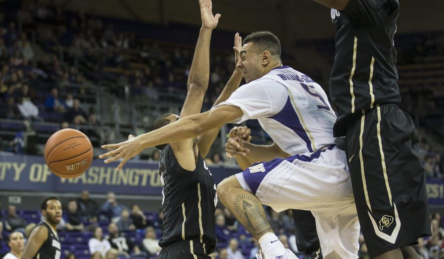Washington's Nigel Williams-Goss, center, passes in traffic as Colorado's Xavier Talton, left, and Wesley Gordon defend during the first half of an NCAA college basketball game Thursday, March 5, 2015, in Seattle. (AP Photo/Stephen Brashear)