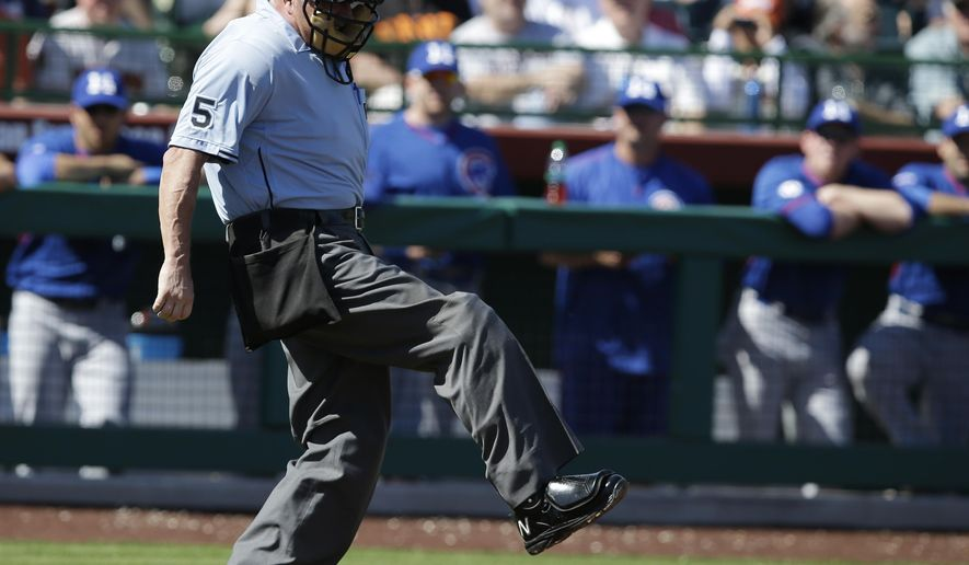 Umpire Dale Scott reacts after getting hit by a baseball during the first inning of a spring training baseball game between the San Francisco Giants and Chicago Cubs Thursday, March 5, 2015, in Scottsdale, Ariz. (AP Photo/Darron Cummings)