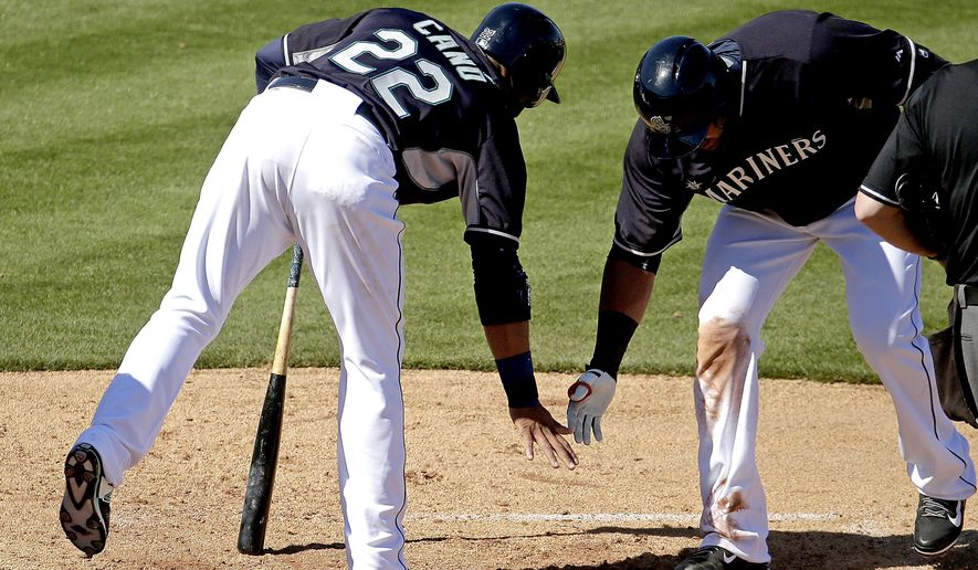 Seattle Mariners' Nelson Cruz , right, celebrates with Robinson Cano (22) after hitting a two-run home run during the third inning of a spring training baseball game against the San Diego Padres Thursday, March 5, 2015, in Peoria, Ariz. (AP Photo/Charlie Riedel)