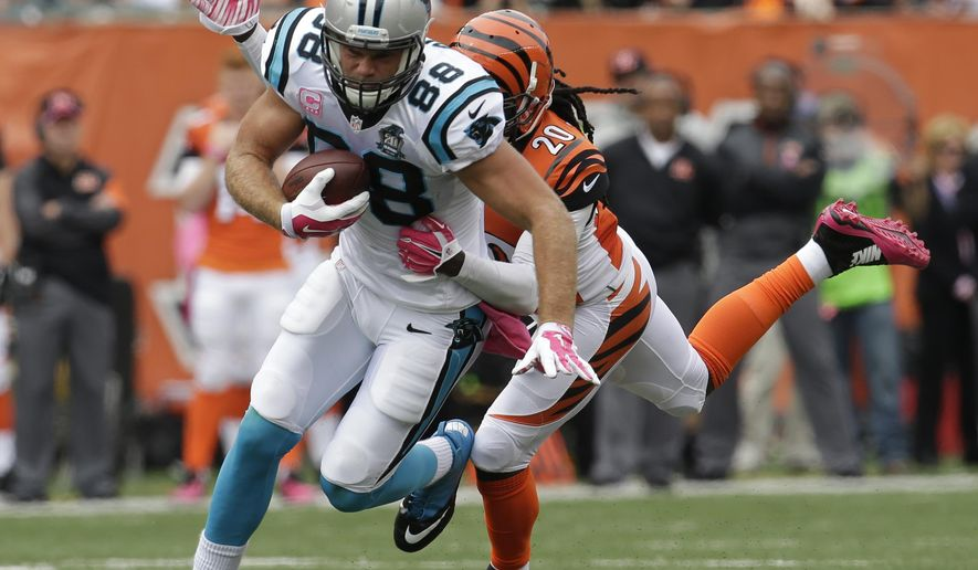 FILE - In this Oct. 12, 2014, file photo, Carolina Panthers' Greg Olsen (88) is tackled by Cincinnati Bengals free safety Reggie Nelson (20) during an NFL football game in Cincinnati. The Panthers announced they have signed Olsen, a Pro Bowl tight end, to a three-year contract extension that will keep him with the team through the 2018 season. The deal is worth $22.5 million overall and includes a $12 million signing bonus, according to his agent Drew Rosenhaus. (AP Photo/AJ Mast, File))