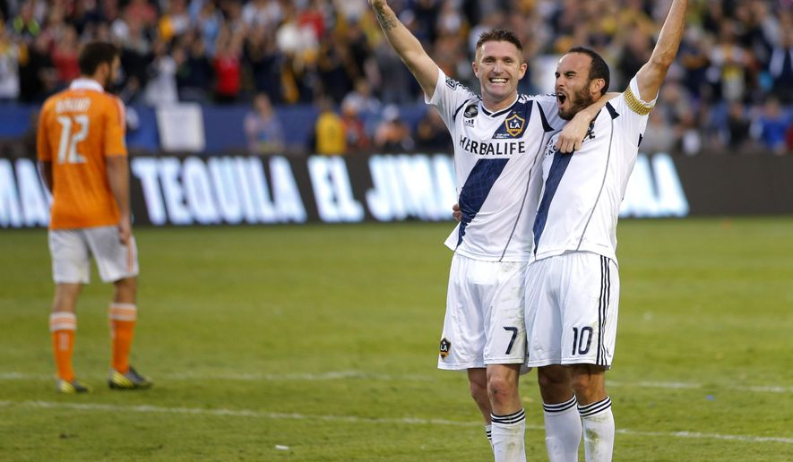 FILE - This Dec. 1, 2012, file photo shows Los Angeles Galaxy's Landon Donovan, right, and Robbie Keane, of Ireland, celebrating their team's 3-1 win as Houston Dynamo's Tally Hall walks off the field after the MLS Cup championship soccer match in Carson, Calif. Donovan is gone for good, and Steven Gerrard won't arrive for four months. Yet when the LA Galaxy begin their MLS Cup title defense Friday, March 6, 2015, this experienced championship team doesn't plan to stumble between the tenures of their former and future scoring stars. (AP Photo/Jae C. Hong,File)
