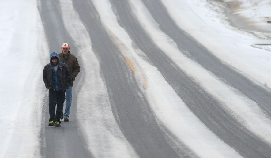 Bobby Simmons and Mark Clark walk up an icy highway 36, after making a trip to the grocery store, as sleet blankets the Hartselle, Ala., area, Thursday, March 5, 2015.   (AP Photo/The Decatur Daily, Gary Cosby Jr.)