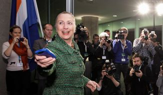 In a photo from Thursday, Dec. 8, 2011, then-U.S. Secretary of State Hillary Rodham Clinton hands off her mobile phone after arriving to meet with Dutch Foreign Minister Uri Rosenthal at the Ministry of Foreign Affairs in The Hague, Netherlands. Clinton urged the State Department to release the emails she wrote from a private email account as secretary of state, weighing in on a controversy that has generated negative attention this week for the likely Democratic presidential candidate. She still hasn't explained why she used her own email server and eschewed a State Department email address. (AP Photo/J. Scott Applewhite, Pool/File) (credit)