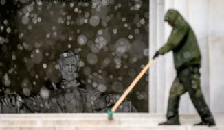 U.S. Park Service maintenance supervisor sweeps snow off stairs at the Lincoln Memorial with the statue of Abraham Lincoln visible in the background on Thursday. As much as 9 inches of snow blanketed the greater D.C. area on Thursday. The National Weather Service has forecasted temperatures in the 50s next week. (associated press)
