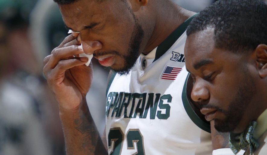 Michigan State's Branden Dawson comes off the floor after an injury during the first half of an NCAA college basketball game against Purdue, Wednesday, March 4, 2015, in East Lansing, Mich. At right is trainer Quinton Sawyer. Michigan State won 72-66. (AP Photo/Al Goldis)