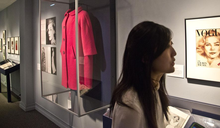 """This March 3, 2015 photo shows student curator Mindy Meissen, left, during a press preview of the exhibition """"Lauren Bacall: The Look,"""" in New York. The exhibition, organized and curated by Fashion Institute of Technology (FIT) graduate  students, explores Bacall's career and personal style, and runs through April 4 at The Museum at FIT.  (AP Photo/Bebeto Matthews)"""