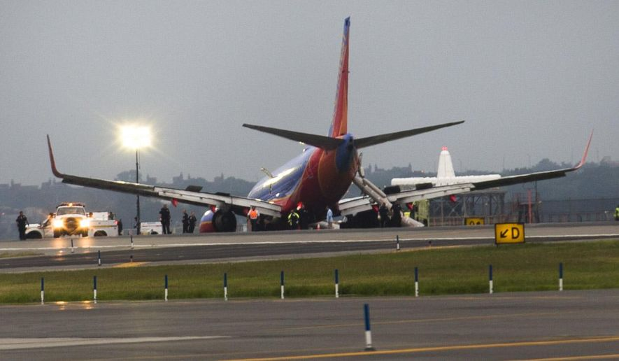 FILE - In this July 22, 2013 file photo, a Southwest Airlines jet rests on the tarmac after what officials say was a nose gear collapse during a landing at LaGuardia Airport. Sixteen passengers and crew members were hurt. Southwest fired the captain and required additional training for the co-pilot. (AP Photo/John Minchillo, File)