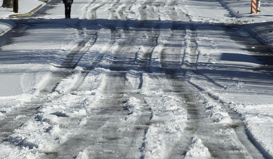 A pedestrian walks alongside tire tracks in the deep snow on Mississippi Ave. in southeast Fort Worth, Texason  Thursday, March 5, 2015.  The National Weather Service issued a winter storm warning for the Dallas-Fort Worth area until midday.  (AP Photo/The Fort Worth Star-Telegram,  Ron T. Ennis)  MAGS OUT; (FORT WORTH WEEKLY, 360 WEST); INTERNET OUT