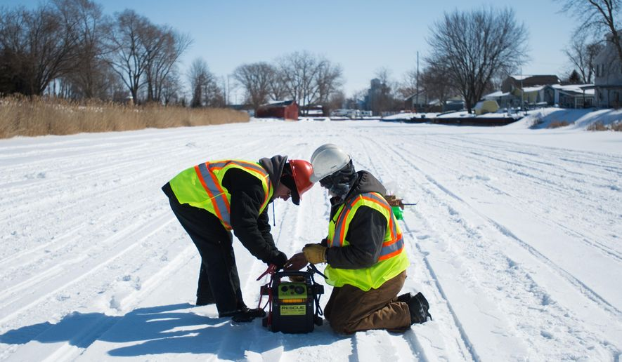 Huron County Road Commission crew set explosives to break up ice in the Sebewaing River to prevent flooding Thursday, March 5, 2015 in the village of Sebewaing, Mich. The workers detonated explosives from the railroad bridge to the mouth of the river that drains to the Saginaw Bay. (AP Photo/The Bay City Times, Yfat Yossifor)