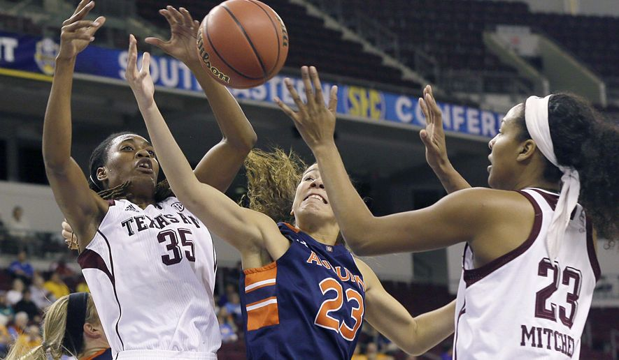Auburn's Jessica Jones (23), center, reaches for the ball with Texas A&M's Achiri Ade (35) and Rachel Mitchell, right,  in the first half of a Southeastern Conference women's tournament NCAA college basketball game in North Little Rock, Ark., Thursday, March 5, 2015. (AP Photo/Danny Johnston)