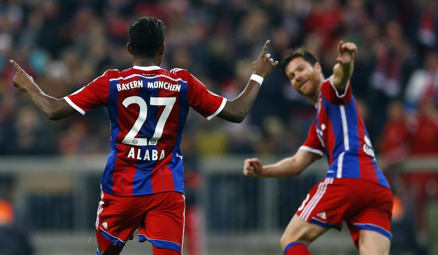 Bayern's David Alaba, left, celebrates with teammate Bayern's Xabi Alonso after scoring his side's opening goal during the German Soccer Cup round of sixteen match between FC Bayern Munich and Eintracht Braunschweig in Munich, southern Germany, Wednesday, March 4, 2015. (AP Photo/Matthias Schrader)