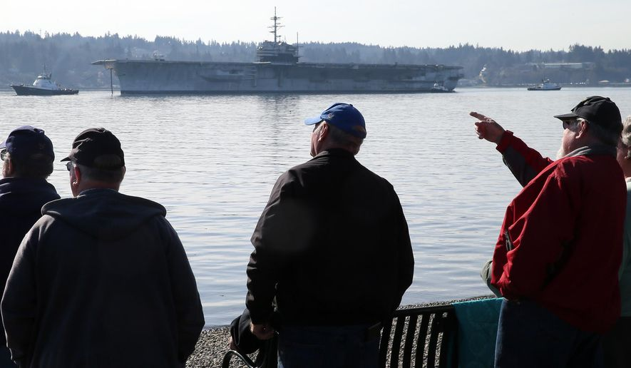 Former crew members and onlookers watch from  Bachmann Park in Manette, Wash., as the USS Ranger is towed from Bremerton Thursday, March 5, 2015. The historic aircraft carrier heads to Texas to be dismantled. (AP Photo/Kitsap Sun, Larry Steagall)