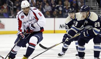 Washington Capitals' Alex Ovechkin (8), of Russia, works for the puck against  Columbus Blue Jackets' Cam Atkinson (13) and Cody Goloubef (29) during the first period of an NHL hockey game in Columbus, Ohio, Tuesday, March 3, 2015. Washington won 5-3. (AP Photo/Paul Vernon)