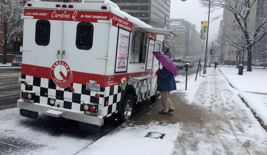Monisha Chakrobortty of Alexandria, Va. waits for a pulled pork sandwich at the Carolina Q food truck in Washington, Thursday, March 5, 2015, one of few food trucks working in the Washington area that decided to brave slippery roads and heavy snow. (AP Photo/Amanda Lee Myers)