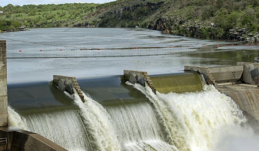 In a March 20, 2012 photo, the LCRA opens floodgates at Starke Dam along the Highland Lakes to ease floodwaters from recent rains that dumped several inches in Central Texas. As some local governments across Central Texas fret over whether they'll have enough of a water supply for growth, Austin appears likely to double down on its ties to the Colorado River. That's because more than 15 years ago, a Kirk Watson-led City Council inked a $100 million agreement to guarantee Colorado River water to Austin through at least 2050. (AP Photo/Austin American-Statesman, Ralph Barrera/)  AUSTIN CHRONICLE OUT, COMMUNITY IMPACT OUT, INTERNET AND TV MUST CREDIT PHOTOGRAPHER AND STATESMAN.COM, MAGS OUT
