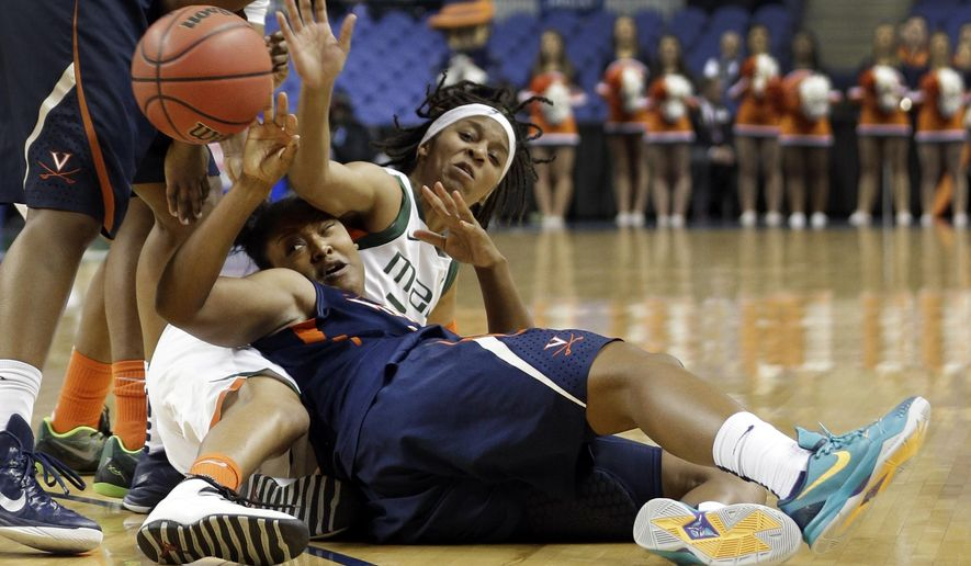 Virginia's Faith Randolph, left, and Miami's Adrienne Motley, right, battle for a loose ball during the first half of an Atlantic Coast Conference women's tournament basketball game in Greensboro, N.C., Thursday, March 5, 2015. (AP Photo/Chuck Burton)