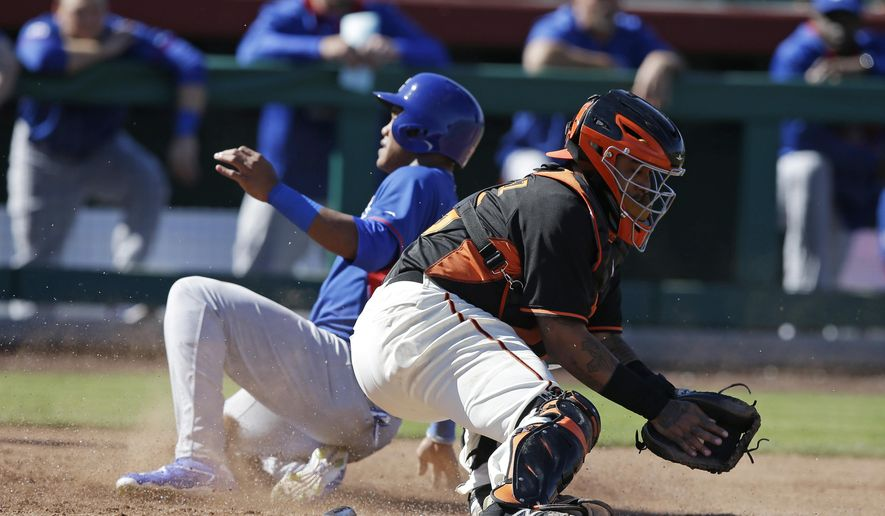 San Francisco Giants' Hector Sanchez (29) takes the throw from Justin Maxwell as Chicago Cubs' Addison Russell (75) slides safe at home during the fifth inning of a spring training baseball game Thursday, March 5, 2015, in Scottsdale, Ariz. Russell scored on sacrifice fly by Arismendy Alcantara. (AP Photo/Darron Cummings)