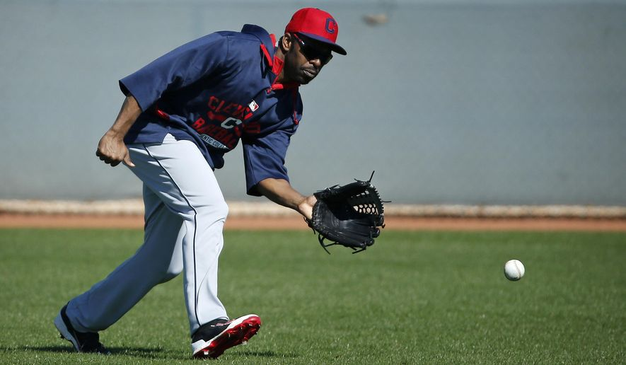 Cleveland Indians' Michael Bourn fields a ball during a workout before a spring training exhibition baseball game against the Cincinnati Reds, Thursday, March 5, 2015, in Goodyear, Ariz. (AP Photo/John Locher)