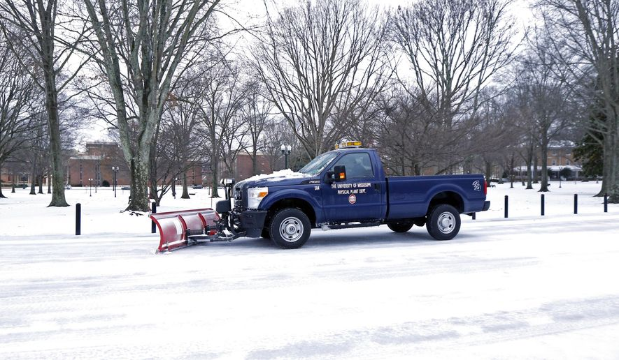 A snowplow moves down a street at the University of Mississippi in Oxford, Miss., as it drives past The Grove, Thursday, March 5, 2015. Sleet and snow continued Thursday morning across a wide belt of Mississippi, even as precipitation ended in the northwest part of the state. (AP Photo/Rogelio V. Solis)