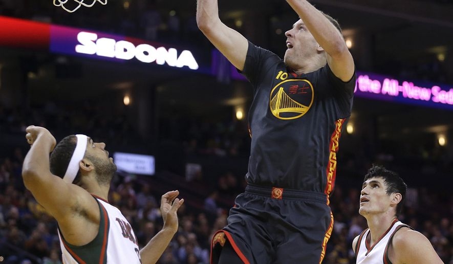 Golden State Warriors' David Lee (10) lays up a shot over Milwaukee Bucks' Jared Dudley, left, during the first half of an NBA basketball game Wednesday, March 4, 2015, in Oakland, Calif. (AP Photo/Ben Margot)