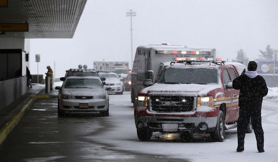Emergency vehicles line up outside of a terminal at LaGuardia Airport in New York, Thursday, March 5, 2015. A plane from Atlanta skidded off a runway at the airport while landing Thursday, crashing through a chain-link fence and sending passengers saddled with bags and bundled up in heavy coats and scarves sliding down an inflated chute to safety on the snowy pavement. (AP Photo/Seth Wenig)