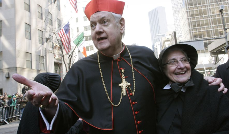 Cardinal Edward Egan, left, shares a moment with Sister Dominica Rocchio of the Sisters of Charity as she and the Sisters of Charity pause in front of St. Patrick's Cathedral on their way up New York's Fifth Avenue during the St. Patrick's Day parade, Tuesday March 17, 2009. (AP Photo/Tina Fineberg)