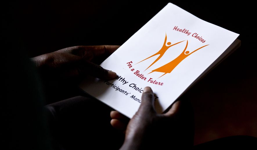 "In this photo taken Monday, Feb. 16, 2015, a child holds a book while attending an HIV prevention session entitled ""Healthy Choices for a Better Future"" to a group comprised of children, adolescents and adults who are either HIV-positive or at high risk of catching HIV due to their circumstances, at a center run by a Kenyan non-governmental organization in the Korogocho slum neighborhood of Nairobi, Kenya. AIDS has become the leading cause of death for adolescents in Africa and the second leading cause of death among adolescents globally, global health agencies said Tuesday. (AP Photo/Ben Curtis)"