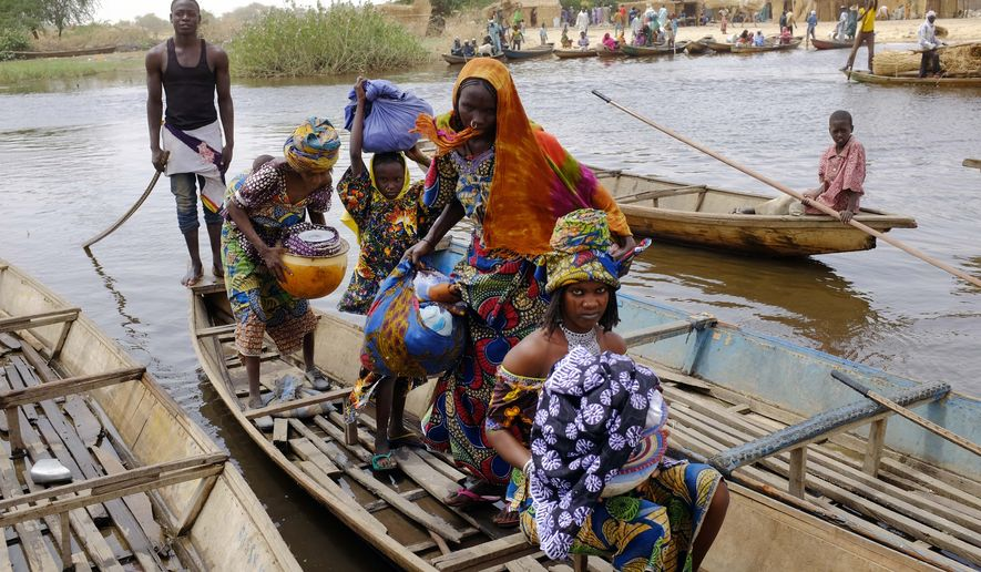 Fulani women cross a tributary of Lake Chad to the village of  N'Gouboua, Thursday, March 5, 2015, using the same route the Nigerian refugees used to flee Boko Haram. Boko Haram militants arrived in N'gouboua before dawn on Feb. 13, marking the first attack of its kind on Chad. By the time the scorched-earth attack ended, they had burned scores of mud-brick houses by torching them with gasoline and had killed at least eight civilians and two security officers. Some 3,400 Nigerian refugees had been living in the village at the time of the attack, and all have since been relocated further inland. (AP Photo/Jerome Delay)