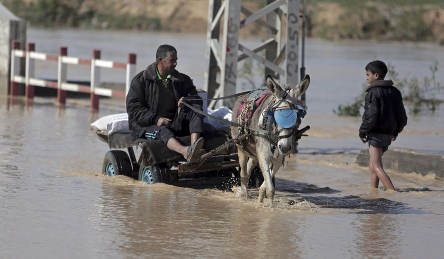 """A man on a donkey cart traverses a rain-flooded street in the central Gaza Strip on Feb. 22, 2015. Palestinian media and officials falsely accused Israel of flooding the area by opening non-existent """"dams."""" (AP Photo/Khalil Hamra)"""