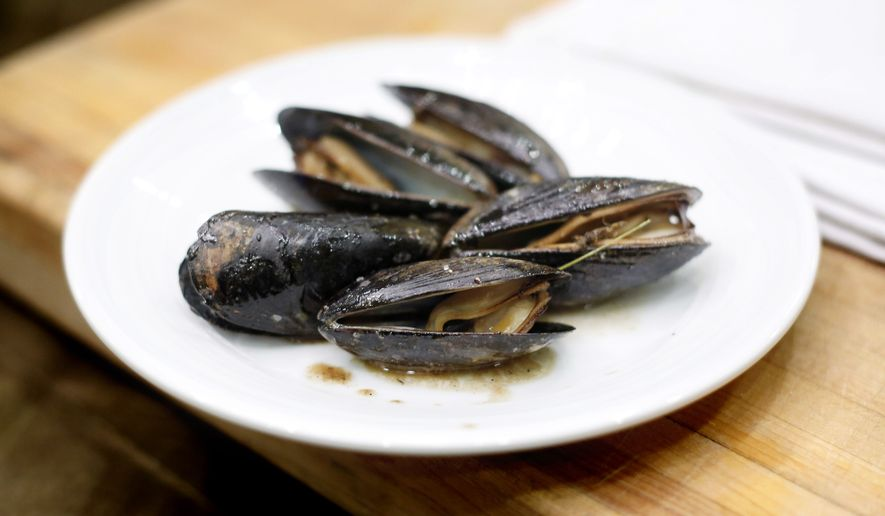 A dish of mussels roasted with pine needles is displayed during a cooking demonstration at the both annual Maine Fishermen's Forum, Thursday, March 5, 2015, in Rockport, Maine.  Maine fishermen set a state record with a catch valued at more than $585 million in 2014. (AP Photo/Robert F. Bukaty)