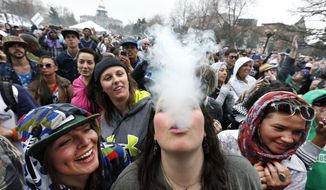 In this April 19, 2014, file photo, partygoers dance and smoke pot during the annual 4/20 marijuana festival in Denver, the state Capitol building visible in the background. (AP Photo/Brennan Linsley, File)