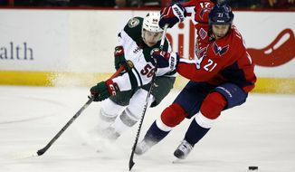 Washington Capitals center Brooks Laich (21) changes direction with the puck, with Minnesota Wild center Erik Haula (56), from Finland, behind him during the third period of an NHL hockey game Thursday, March 5, 2015, in Washington. The Wild won 2-1. (AP Photo/Alex Brandon)