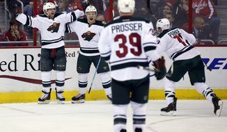 Minnesota Wild right wing Jason Pominville, left, celebrates his goal with center Mikael Granlund (64), from Finland, as defenseman Nate Prosser (39) and left wing Zach Parise (11) come to join, during the third period of an NHL hockey game against the Washington Capitals, Thursday, March 5, 2015, in Washington. The Wild won 2-1. (AP Photo/Alex Brandon)