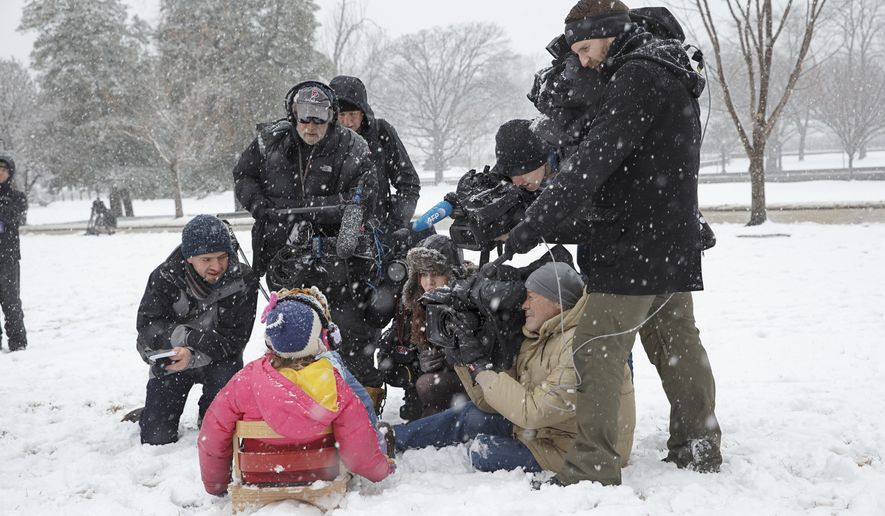 Members of the media gather around a young sledder in the falling snow on Capitol Hill in Washington, Thursday, March 5, 2015. Despite failing to get permission from congressional officials, scores of residents of the community around the Capitol flocked to the building's slopey West Lawn on Thursday for an afternoon of sled riding in the shadow of the famous Dome. (AP Photo/J. Scott Applewhite)