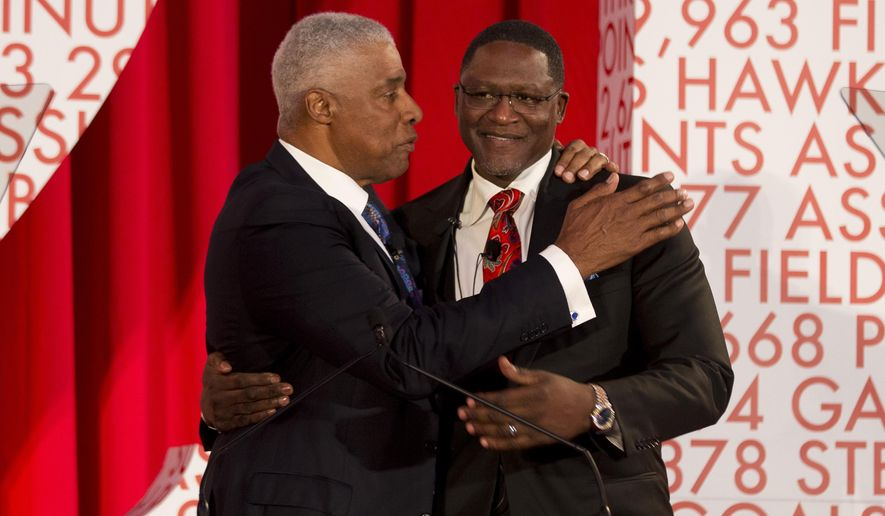 Former Atlanta Hawks star and NBA Hall of Famer Dominique Wilkins, right,  embraces Julis Erving  as a 13-foot statue of Wilkins is unveiled at Philips Arena  Thursday, March 5, 2015, in Atlanta. (AP Photo/John Bazemore, Pool)