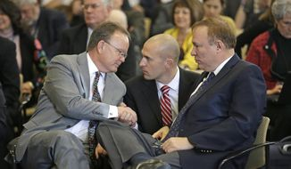 Eric Moutsos, center, the former Salt Lake Police officer who was placed on leave and later resigned for not wanting to ride his motorcycle in the Salt Lake gays pride parade for religious reasons, shakes hands with Sen. Stuart Adams, R-Layton, left, while Sen. Jim Dabakis, D-Salt Lake City, looks on during a committee hearing Thursday, March 5, 2015, in Salt Lake City. (AP Photo/Rick Bowmer)