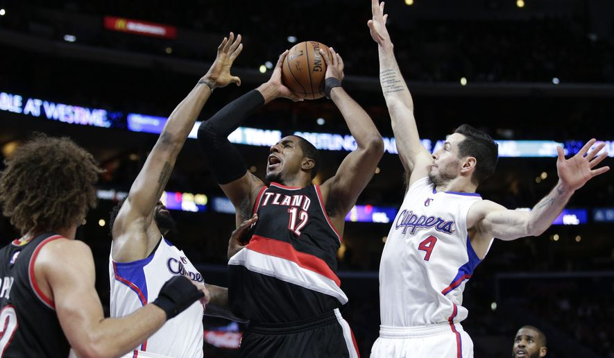 Portland Trail Blazers' LaMarcus Aldridge, center, goes up for a basket as he is defended by Los Angeles Clippers' DeAndre Jordan, left, and J.J. Redick during the second half of an NBA basketball game, Wednesday, March 4, 2015, in Los Angeles. The Trail Blazers won 98-93 in overtime. (AP Photo/Jae C. Hong)