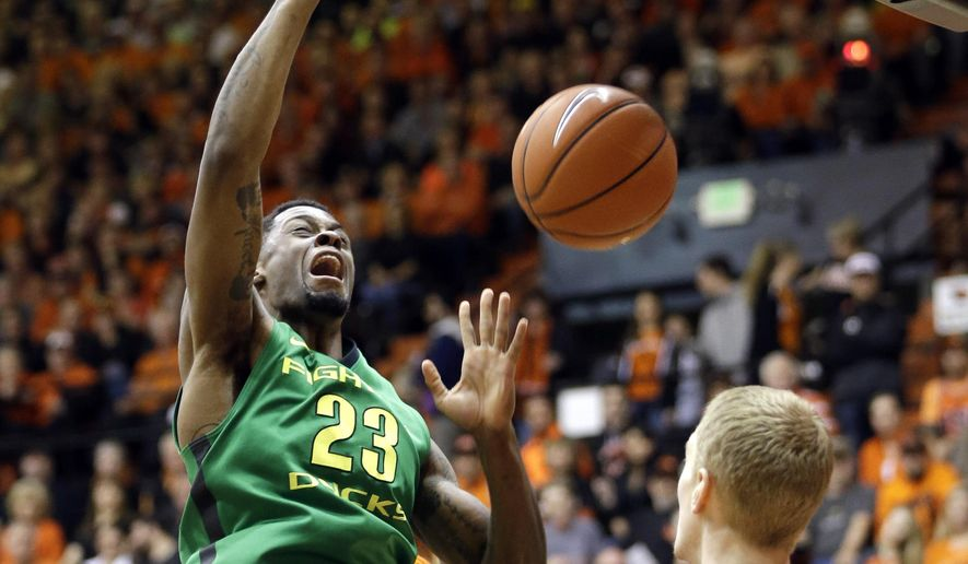 Oregon forward Elgin Cook, left, scores in front of Oregon State forward Olaf Schaftenaar during the first half of an NCAA college basketball game in Corvallis, Ore., Wednesday, March 4, 2015. (AP Photo/Don Ryan)