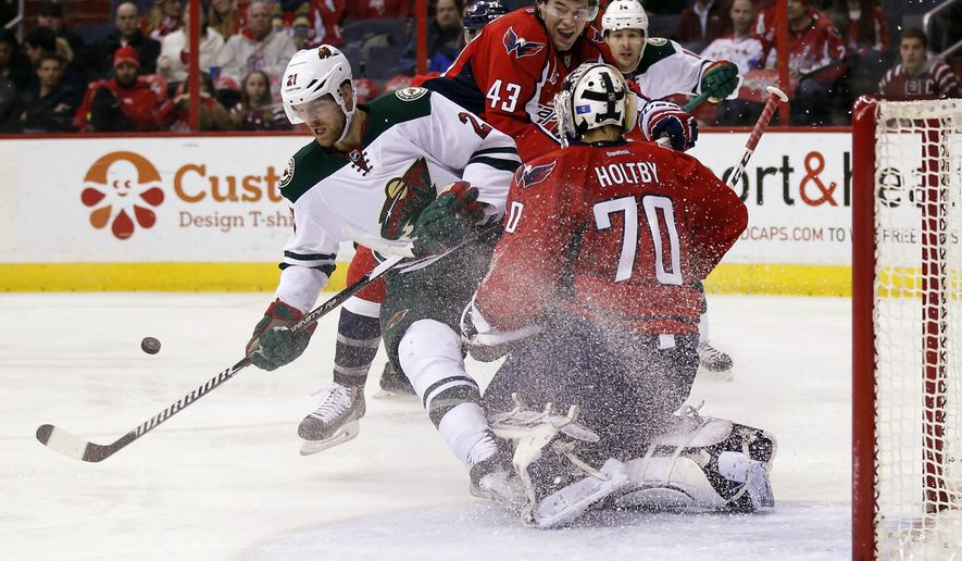 Minnesota Wild center Kyle Brodziak (21) can't get the puck that was deflected by Washington Capitals goalie Braden Holtby (70), with right wing Tom Wilson (43) nearby, during the second period of an NHL hockey game Thursday, March 5, 2015, in Washington. (AP Photo/Alex Brandon)