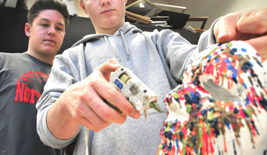 In a Feb. 2015 photo, Cameron McCool watches while Fred Hall pushes broken crayon pieces through a hot glue gun and onto a plaster mask in Mary Hall's art classroom at Suttons Bay High School in Suttons Bay, Mich. The pair plus Eric Hutton are working to create a work of clothing art from used office and school materials. (AP Photo/Traverse City Record-Eagle, Nathan Payne)