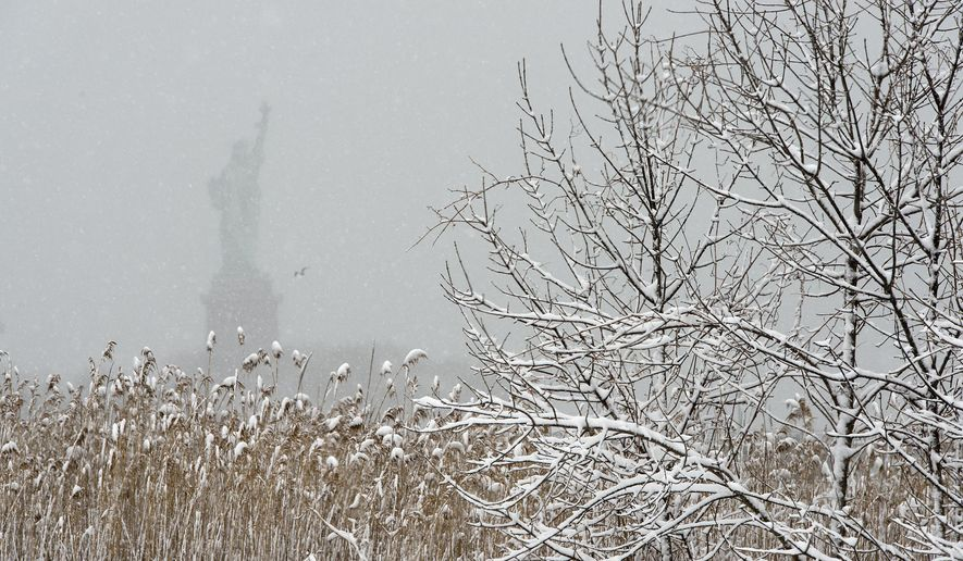 The Statue of Liberty is barely visible through snow falling at Liberty State Park in Jersey City during a winter storm on Thursday, March 5, 2015. (AP Photo/The Jersey Journal, Reena Rose Sibayan)