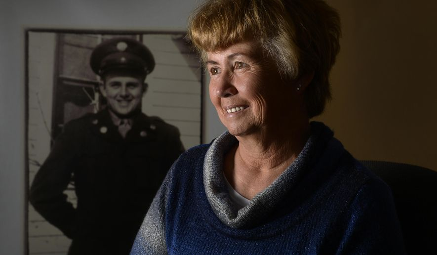 In this photo taken Tuesday, March 3, 2015, JoAnn Mueller pose for a photo in Sheridan, Colo., next to a portrait of her uncle Sgt. Floyd Jackson, who died in a POW camp during the Korean War. The family will honor him this week after his remains will arrive home in Colorado on Thursday, march 5, and will be buried next to his mother and near his brother and sister in a cemetery in Centennial on Saturday. (AP Photo/The Denver Post, Kathryn Scott Osler) MAGS OUT; TV OUT; INTERNET OUT; NO SALES; NEW YORK POST OUT; NEW YORK DAILY NEWS OUT